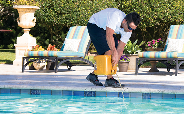 pool technician pouring chloring